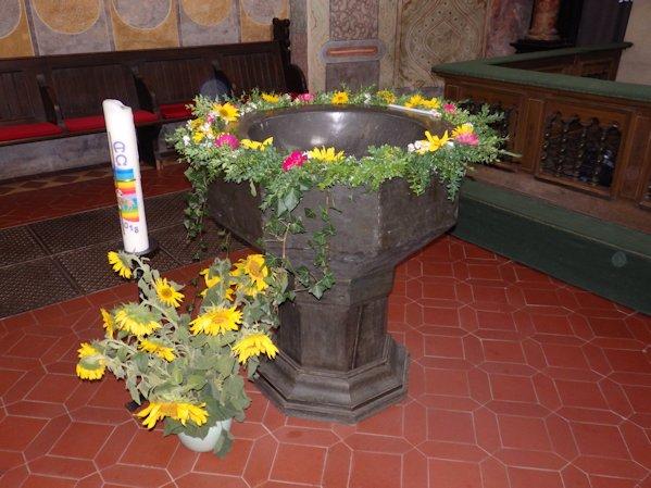 Taufstein geschmückt und mit Osterkerze