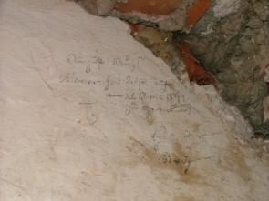 Inschrift, mit Bleistift geschrieben, hinter zugemauerter Tür.